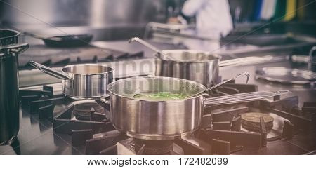 Different pots cooking on hotplate in professional kitchen