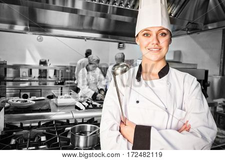 Smiling female chef holding ladle in commercial kitchen