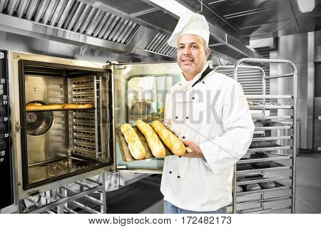 Mature baker showing three baguettes standing in front of an oven