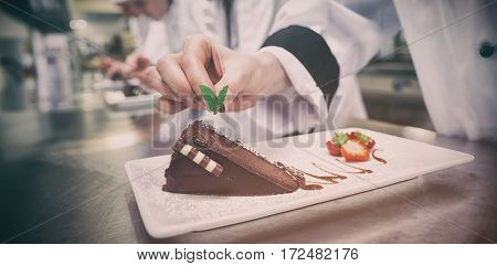 Close up of chef putting mint leaf on chocolate cake in kitchen