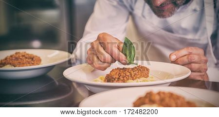 Closeup mid section of a male chef garnishing food in the kitchen