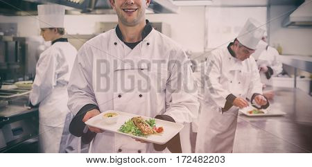 Happy chef holding salmon dish in kitchen