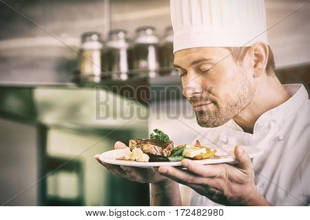 Closeup of a male chef with eyes closed smelling gourmet food in the kitchen