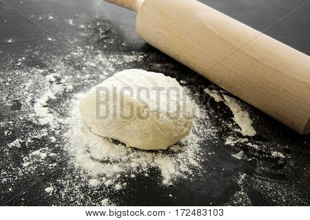 Dough and rolling pin on worktop