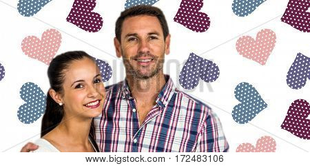 Portrait of smiling couple looking at camera against background with hearts