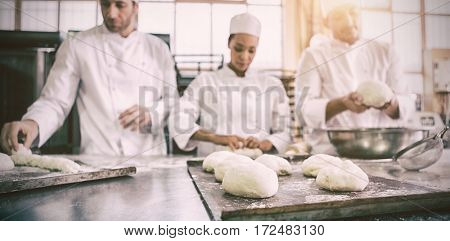 Serious colleagues kneading uncooked dough in the kitchen of the bakery