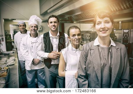 Portrait of female manager posing with staff at kitchen