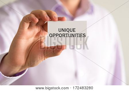 Businessman Holding A Card With Text Unique Opportunities