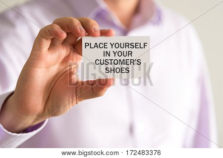 Businessman Holding A Card With Text Place Yourself In Your Customers Shoes
