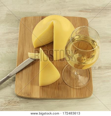 A square photo of tetilla, a traditional Spanish soft cow milk cheese, with a slice cut off, and a glass of white wine, on a wooden board
