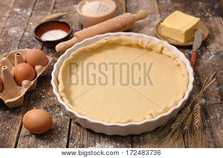 raw dough with rolling pin and flour