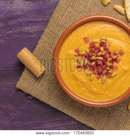A square photo of salmorejo, traditional Spanish cold soup, with bread sticks, crumbs, and a wine cork, shot from above on a burlap and deep purple wooden texture