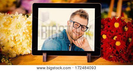 Digital tablet and fresh flowers against handsome designer smiling at camera at his desk