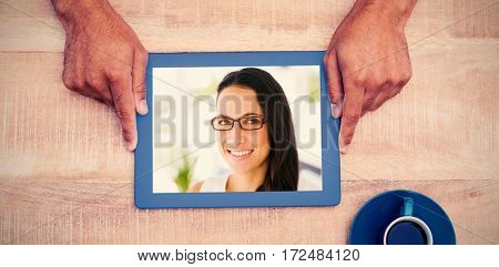 Hand holding on digital tablet over table by coffee against pretty designer smiling at camera