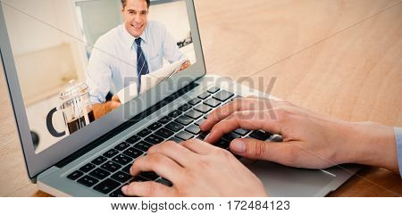 Smiling well dressed man with coffee cup and newspaper in kitchen against businesswoman using laptop