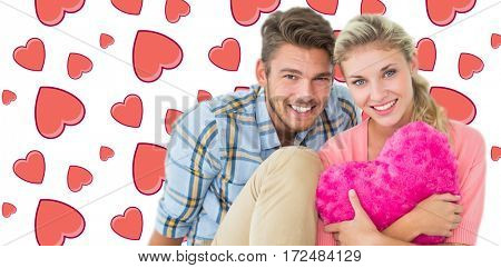Attractive young couple sitting holding heart cushion against background with hearts