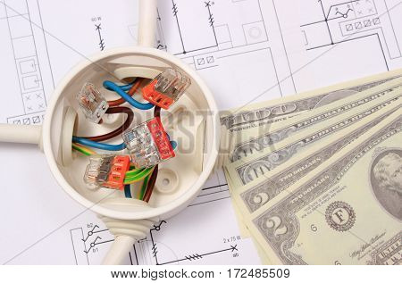 Copper wire connections in electrical box and money on construction drawing of house concept of engineering and energy savings