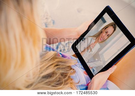 Woman sitting on beach in deck chair using tablet pc against smiling woman holding mug and newspaper