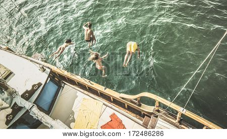 Aerial view of young people jumping from sailing boat on sea trip - Rich happy friends having fun in summer sailboat party day - Exclusive luxury vacation concept - Retro contrast desaturated filter