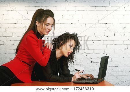 Young women holding credit card make purchases using laptop. Online store