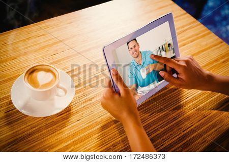 Man with newspaper holding coffee cup at table against woman using digital tablet with blank screen at table in cafe