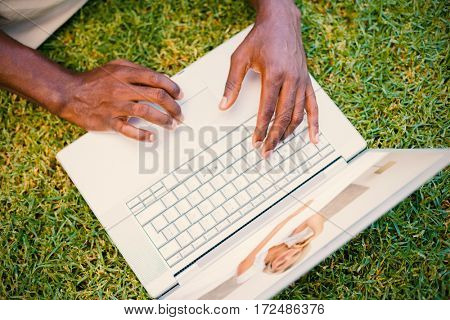 Pretty smiling mature woman sitting on bed against person using laptop on grass