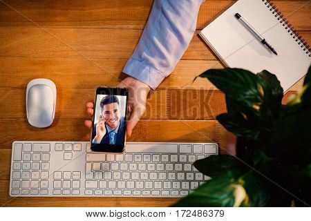 Businessman sitting making a call smiling at camera against cropped image of hand holding mobile phone