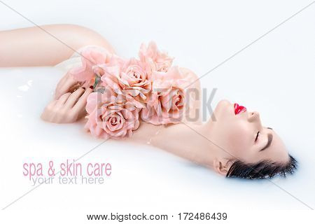 Spa beauty model girl taking milk bath, spa and skin care concept. Beauty young Woman with bright makeup and pink rose flower relaxing in milk bath. Rejuvenation. Treatment. Skincare