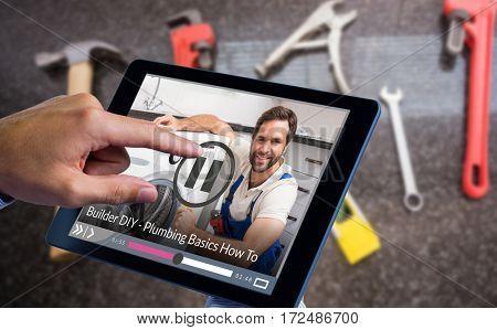 Man using tablet pc against portrait of handyman fixing washing machine