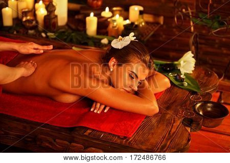 Massage of woman in spa salon. Girl on candles background in massage and skincare spa salon. Luxary interior with white rose in oriental therapy salon. Female bare back with smooth skin have relax .