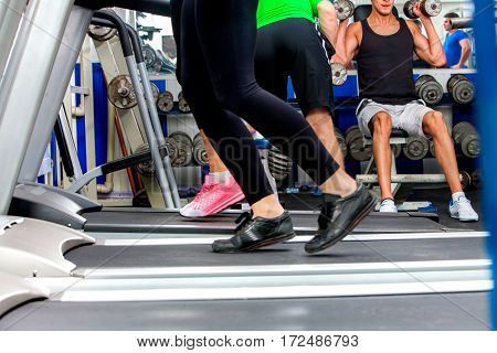 Treadmill and group of legs wearing sneakers running on group people at sport gym background.