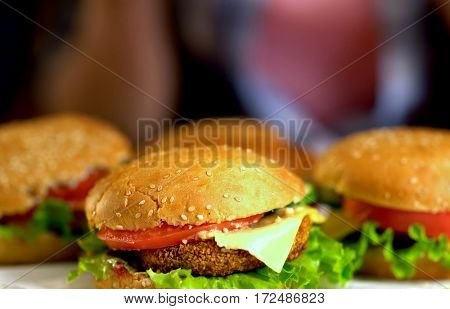 Hamburger fast food with ham on wooden board . Group of hamburger. Human hand holding cheeseburger is not in field. Treats for friendly parties.