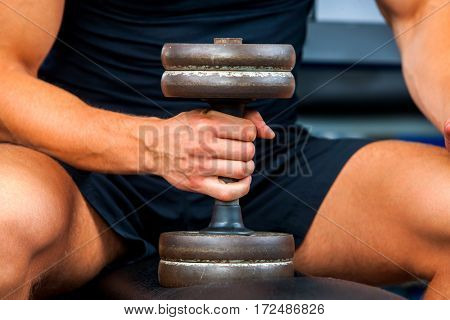Man in gym workout with fitness equipment. Man holding dumbbell workout at gym. Chrome dumbbells in strong male hands.