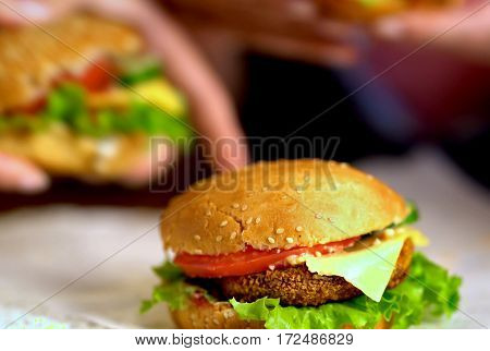 Hamburger fast food with ham on wooden board . Group of hamburger. Human hand holding cheeseburger. Sharpness in front of sandwich.