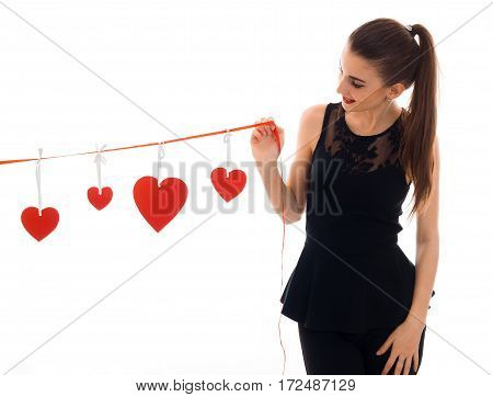 a young girl in a black dress holding a Ribbon with hearts isolated on white background