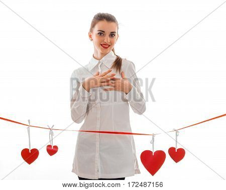young girl in white clothes standing near ribbons with hearts isolated on white background