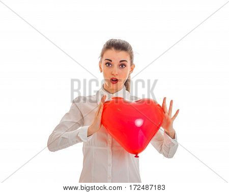 surprised young girl in white shirt holding a large inflatable balloon sweetheart isolated on white background