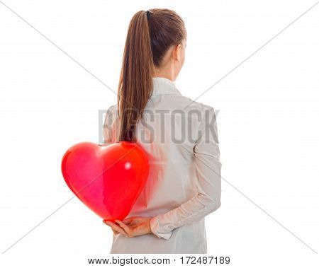 a young girl holds in his hand behind the big red heart shaped balloon isolated on white background
