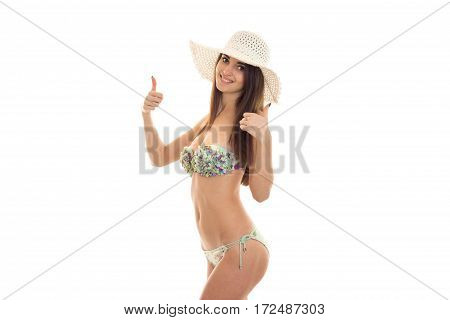 a young girl in a bathing suit and hat worth turning sideways and shows the class of isolated on white background