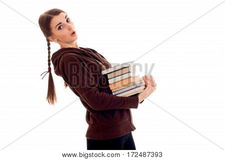 young girl-teen stands sideways and holds many books isolated on white background