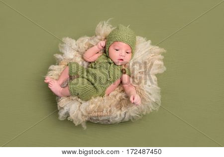 Funny baby in knitted costume in a lovely pose, resting on a furry big pillow