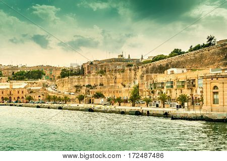 gorgeous Valletta cityscape with yellow stone embankment, view from the sea, Malta