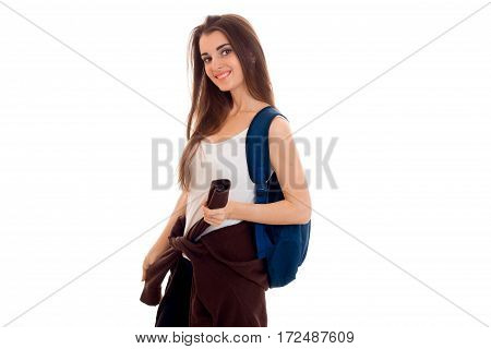 Merry girl stands sideways and keep the Backpack on your shoulder is isolated on a white background