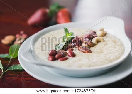 Bowl of oatmeal porridge with nuts and greens, hot and healthy food for Breakfast, close up