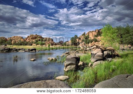 A view from the shore of Watson Lake with blue cloud filled sky and green trees with rock cliffs in Prescott Arizona.