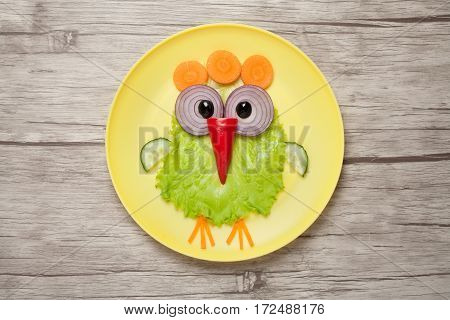 Funny chicken made of vegetables on plate and desk