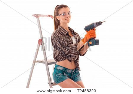 a young girl in a Plaid Shirt and glasses holding a drill near the stairs standing isolated on white