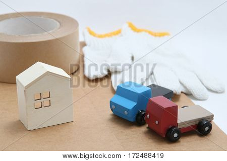 Toy mini car trucks, packing tape, card boards, cotton work gloves and house on white background. Distribution concept.