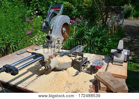 Circular saw and other tools on the background of nature in summer