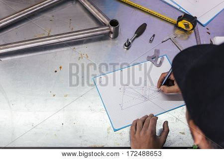 Professional craftsman drawing bicycle on metal table. Overhead.
